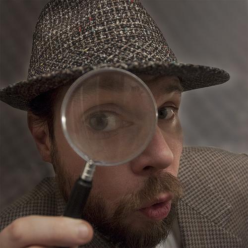 虫眼鏡をのぞき込む男性