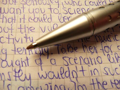 ペンと文字がびっしり書き込まれたノート