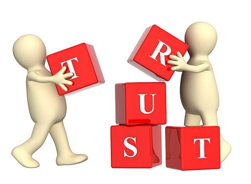 Trustと書かれたブロックを積み上げる人