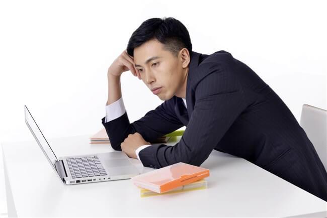 パソコンの画面を見ながら悩む男性