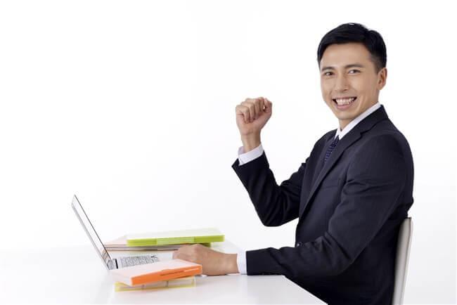 パソコンの前でガッツポーズをする男性